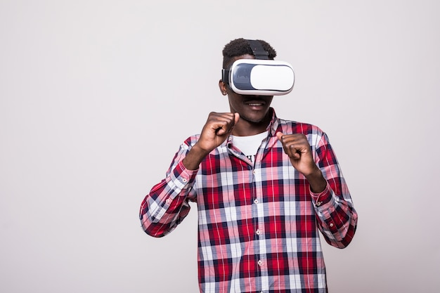 Jovem afro-americano, feliz e animado, usando óculos de realidade virtual de realidade virtual, jogando videogame Foto gratuita