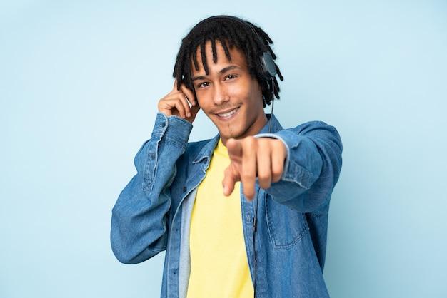 Jovem afro-americano isolado na parede azul, ouvindo música e apontando para a frente Foto Premium