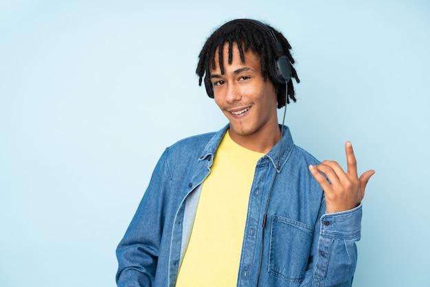 Jovem afro-americano isolado na parede azul, ouvindo música e fazendo gesto de guitarra Foto Premium
