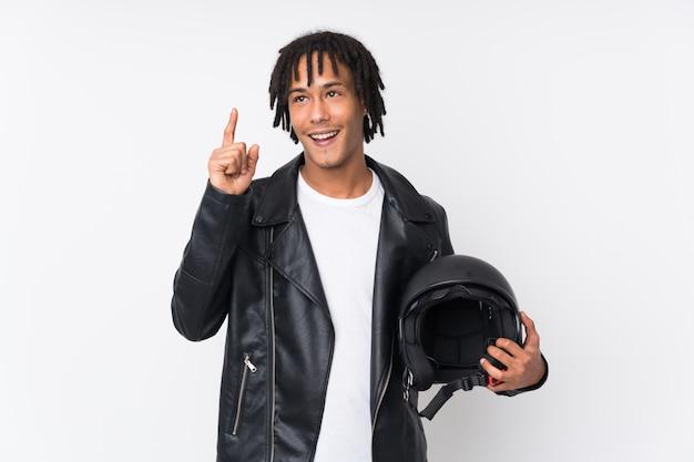 Jovem afro-americano segurando um capacete de moto isolado no branco com a intenção de perceber a solução enquanto levanta um dedo Foto Premium
