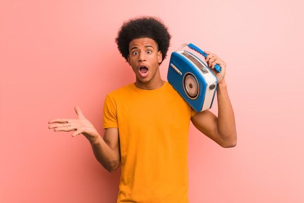 Jovem afro-americano segurando um rádio vintage comemorando uma vitória ou sucesso Foto Premium