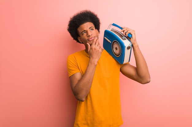 Jovem afro-americano segurando um rádio vintage duvidando e confuso Foto Premium