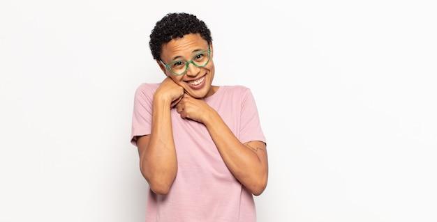 Jovem afro se sentindo apaixonada e bonita, adorável e feliz, sorrindo romanticamente com as mãos ao lado do rosto Foto Premium