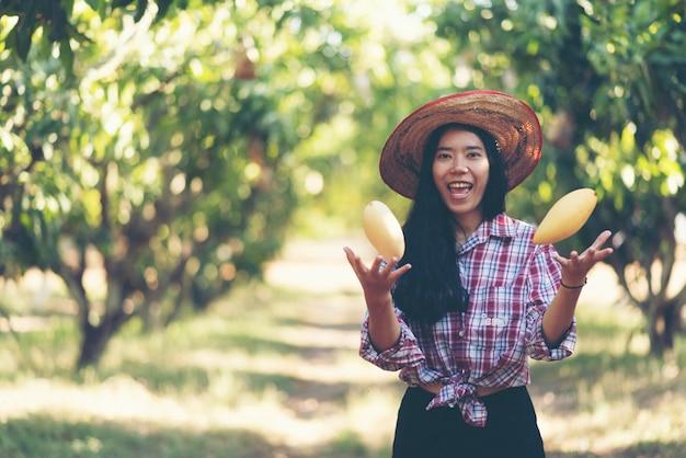 Jovem agricultor asiático colhendo frutas manga na fazenda orgânica Foto Premium