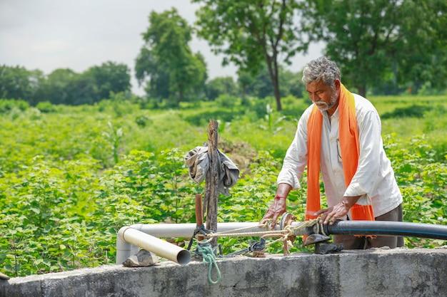 Jovem agricultor indiano trabalhando no campo Foto Premium