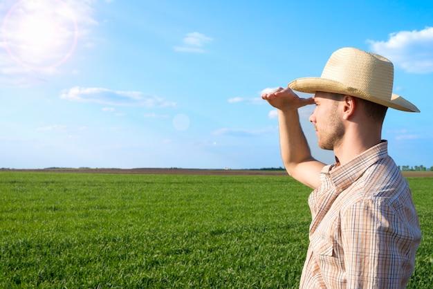 Jovem agricultor no campo observando as colheitas Foto gratuita
