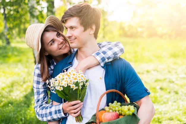 Jovem alegre abraçando amante no parque Foto gratuita