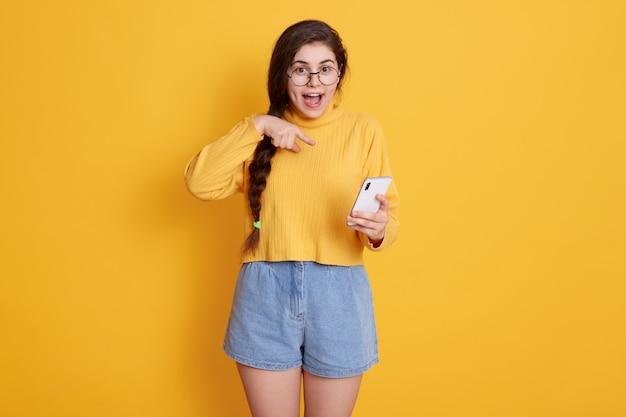 Jovem alegre apontando para o telefone inteligente na mão com expressão facial animada, mantém a boca aberta, vestindo suéter e curto, garota com longos cabelos escuros e trança. Foto Premium