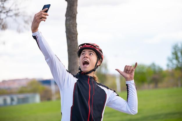 Jovem alegre ciclista masculina no sportswear e capacete mostrando sinal de mão shaka e tomando selfie em smartphone no parque Foto Premium