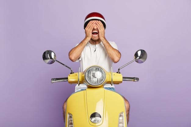 Jovem alegre com capacete dirigindo uma scooter amarela Foto gratuita