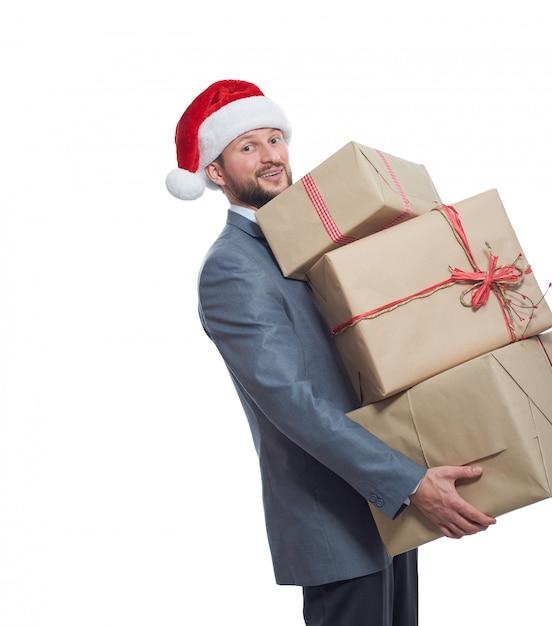 Jovem alegre com um chapéu de natal segurando uma grande pilha de caixas de presente sorrindo Foto gratuita