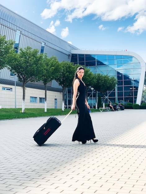 Jovem alegre com uma mala. viagens e trabalho Foto Premium