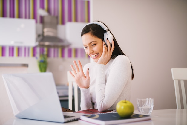 Jovem alegre e feliz está acenando para uma pessoa com quem está estudando on-line enquanto usa o fone de ouvido. Foto Premium