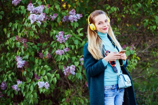 Jovem alegre está ouvindo a música em pé na frente do arbusto lilás Foto Premium