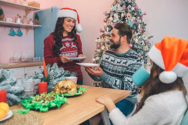 Jovem alegre fica em tabel e sorrindo. ela segura pratos nas mãos. mulher os dá ao marido. ele olha para ela e sorri. filha sentar à mesa também. eles jantam festivamente. Foto Premium