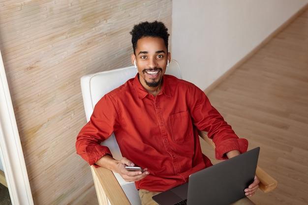 Jovem alegre morena de olhos castanhos barbudo homem de pele escura olhando alegremente com um sorriso encantador enquanto trabalhava fora do escritório com seu telefone celular e laptop Foto gratuita