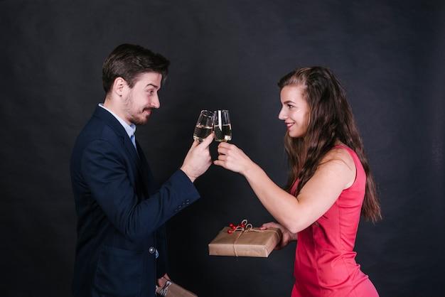 Jovem, alegre, mulher, agarrar, óculos, de, bebida, com, homem, e, segurando, presente, caixas Foto gratuita