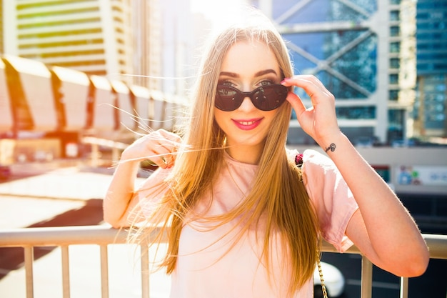 Jovem alegre olha sobre seus óculos de sol posando sob o Foto gratuita
