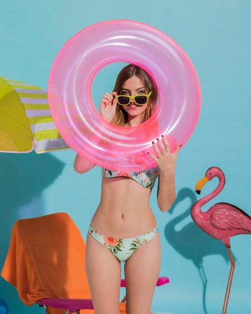 Jovem alegre olhando através de círculo flutuante no estúdio Foto gratuita