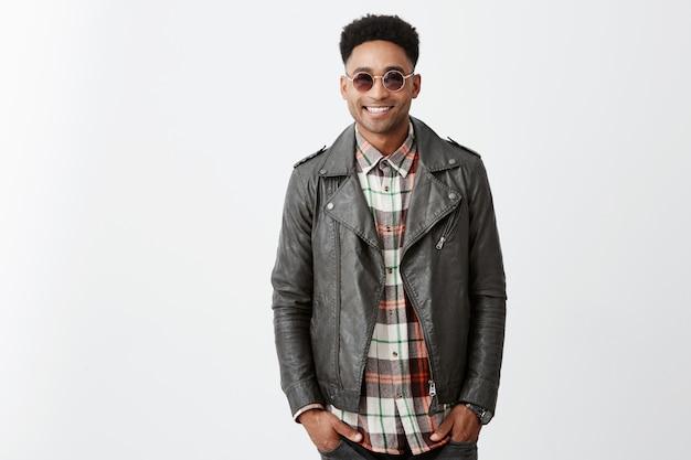 Jovem alegre pele bronzeada homem bonito com cabelo encaracolado na jaqueta de couro elegante e óculos de sol sorrindo segurando as mãos nos bolsos Foto gratuita