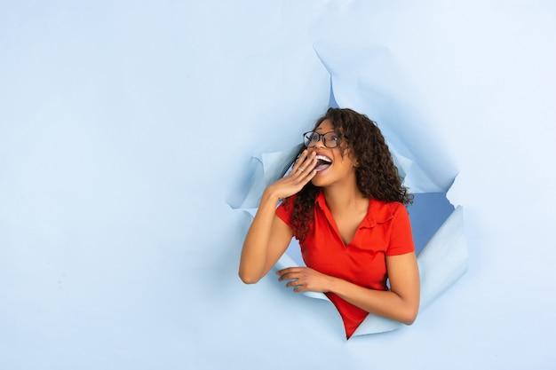 Jovem alegre posa no fundo do buraco de papel azul rasgado, emocional e expressivo Foto gratuita