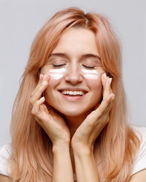 Jovem alegre positiva aplicar creme hidratante lifting nutritivo ou tratamento facial Foto Premium