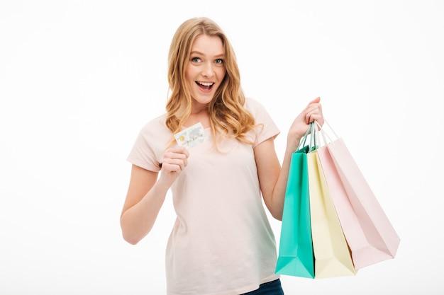 Jovem alegre segurando o cartão de crédito e sacolas de compras. Foto gratuita