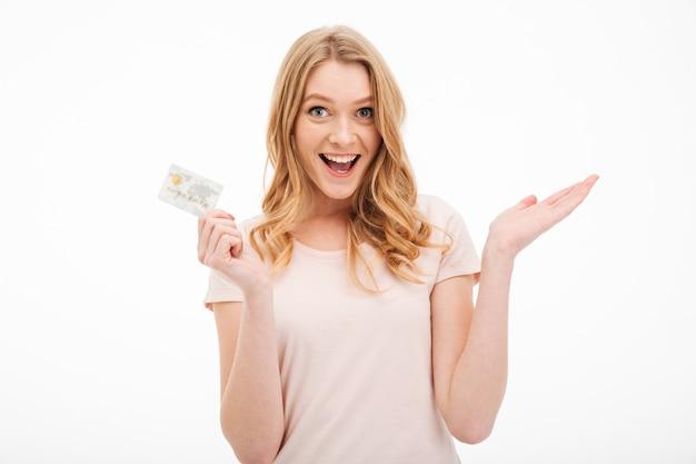 Jovem alegre segurando o cartão de crédito. Foto gratuita