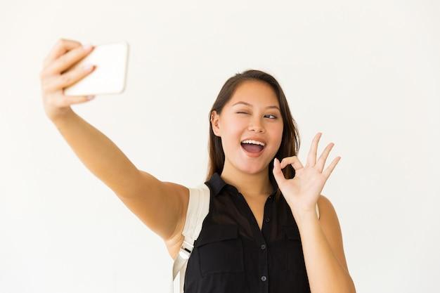 Jovem alegre tomando selfie com smartphone Foto gratuita