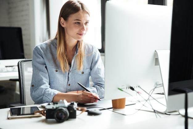 Jovem alegre trabalhar no escritório usando o computador Foto gratuita