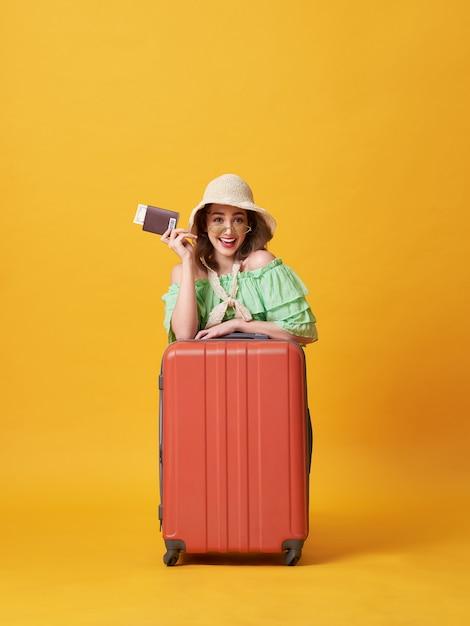 Jovem alegre, vestida com roupas de verão, segurando um passaporte com dinheiro Foto Premium