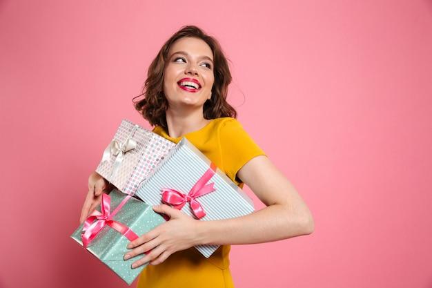 Jovem alegre vestido amarelo segurando a pilha de presentes Foto gratuita