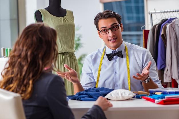 Jovem alfaiate trabalhando com cliente do sexo feminino Foto Premium