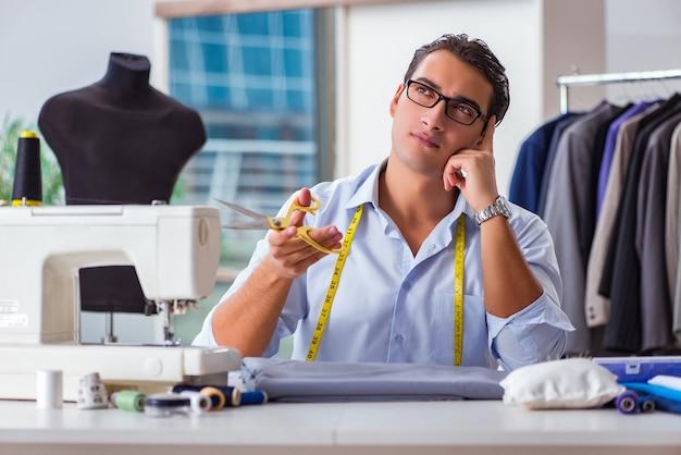 Jovem alfaiate trabalhando em roupas novas Foto Premium