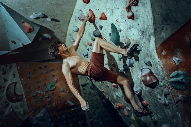 Jovem alpinista grátis escalando pedra artificial dentro de casa Foto gratuita