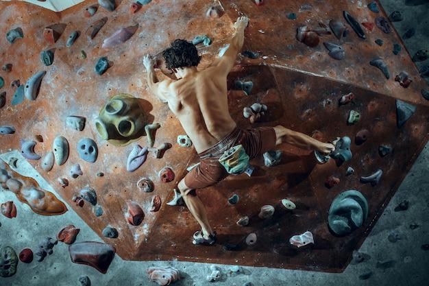 Jovem alpinista livre escalada pedregulho artificial dentro de casa. Foto gratuita