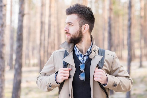 Jovem alpinista masculina com sua mochila, olhando para longe Foto gratuita