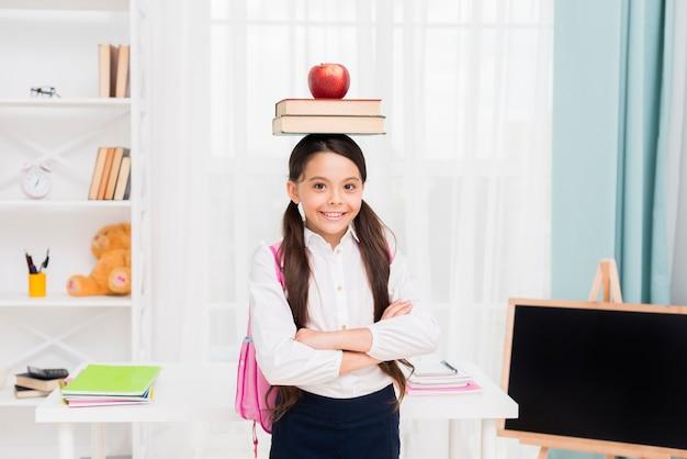 Jovem, aluna, em, uniforme, ficar, braços cruzaram, em, sala aula Foto gratuita
