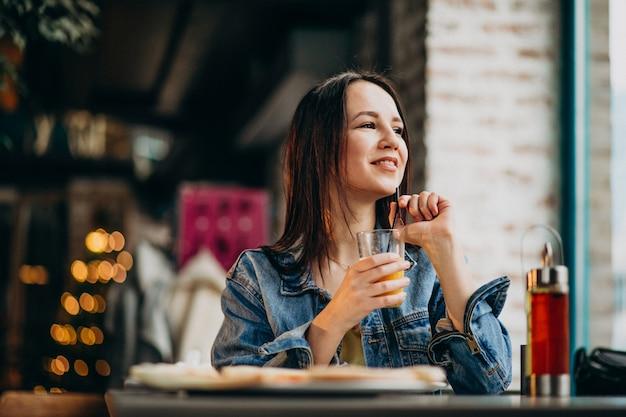Jovem aluna trabalhando no laptop em bar e comendo pizza Foto gratuita