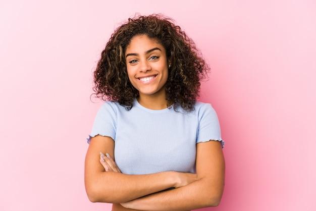 Jovem americana africano contra uma parede rosa que se sente confiante, cruzando os braços com determinação. Foto Premium