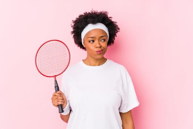 Jovem americana africano jogando badminton isolado confuso, sente-se duvidoso e inseguro. Foto Premium