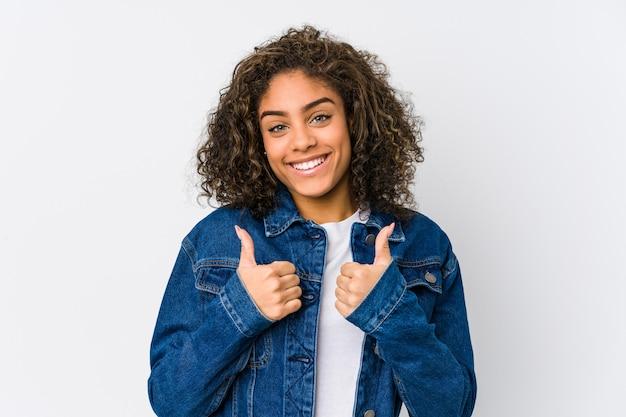 Jovem americana africano, levantando os dois polegares, sorrindo e confiante. Foto Premium