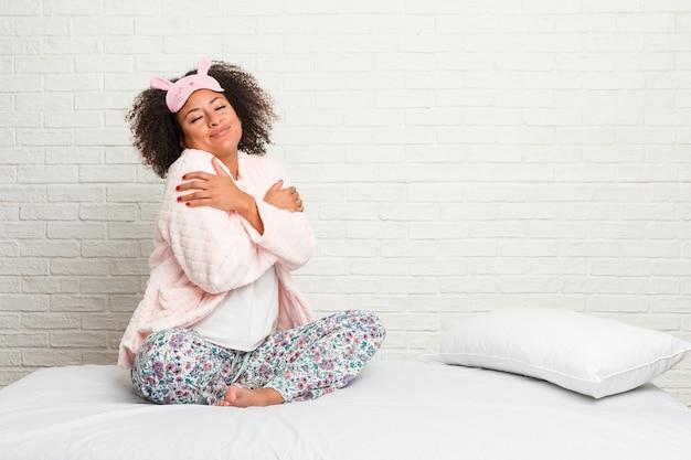 Jovem americana africano na cama vestindo pijama abraços, sorrindo despreocupado e feliz. Foto Premium