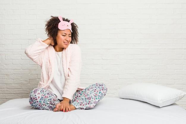 Jovem americana africano na cama vestindo pijama, sofrendo dores no pescoço devido ao estilo de vida sedentário. Foto Premium