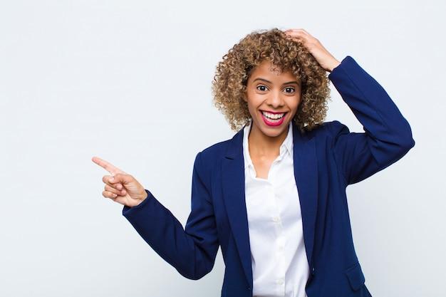 Jovem americana africano rindo, olhando feliz, positivo e surpreso, percebendo uma ótima idéia apontando para o espaço da cópia lateral contra a parede plana Foto Premium