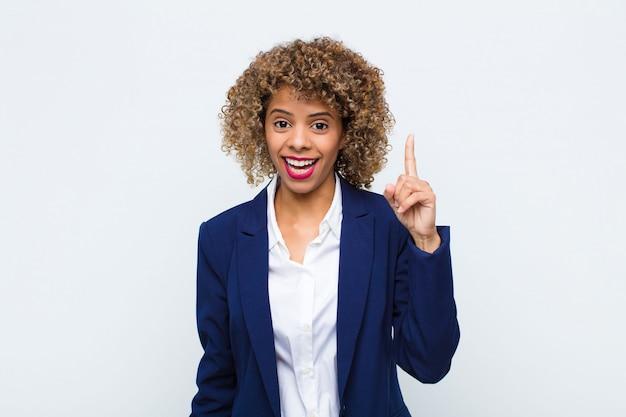 Jovem americana africano se sentindo como um gênio feliz e animado depois de perceber uma idéia, alegremente levantando o dedo, eureka! contra a parede Foto Premium