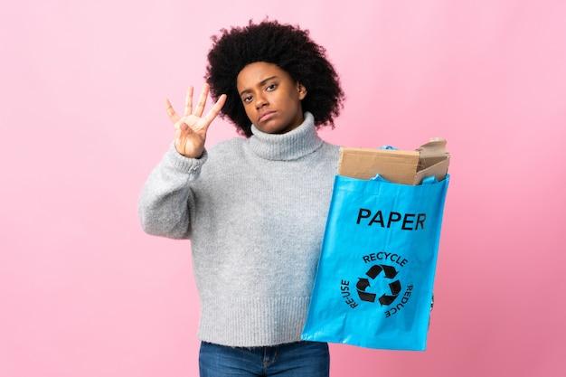 Jovem americana africano segurando uma sacola isolada em fundo colorido feliz e contando quatro com os dedos Foto Premium
