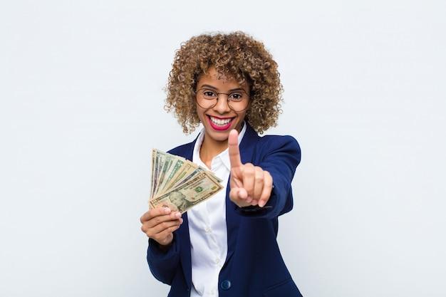Jovem americana africano sorrindo orgulhosa e confiante, fazendo o número um posar triunfante, sentindo-se como um líder com notas de euro Foto Premium