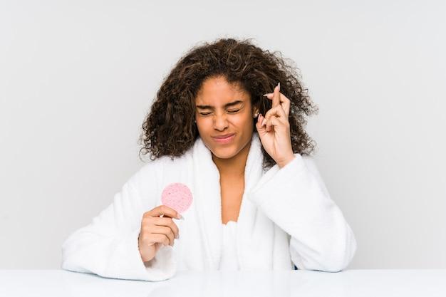 Jovem americana africano usando um disco facial, cruzando os dedos para ter sorte Foto Premium