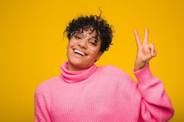 Jovem americana africano vestindo uma blusa rosa alegre e despreocupada, mostrando um símbolo de paz com os dedos. Foto Premium